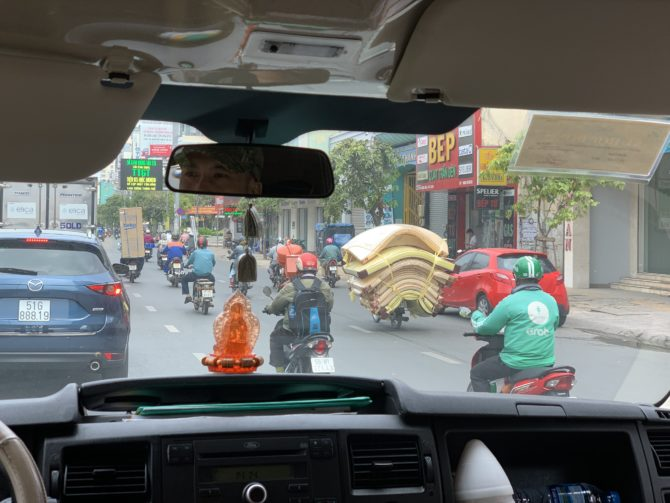 A good illustration of motorbike craziness. Note the mattresses but also the guy with the fridge! Another man drove carrying a tray of food in one hand.